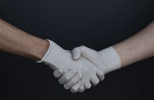 People in plastic gloves shaking hands