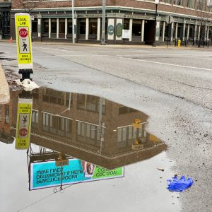 A puddle reflects a building and a billboard in downtown Kalamazoo