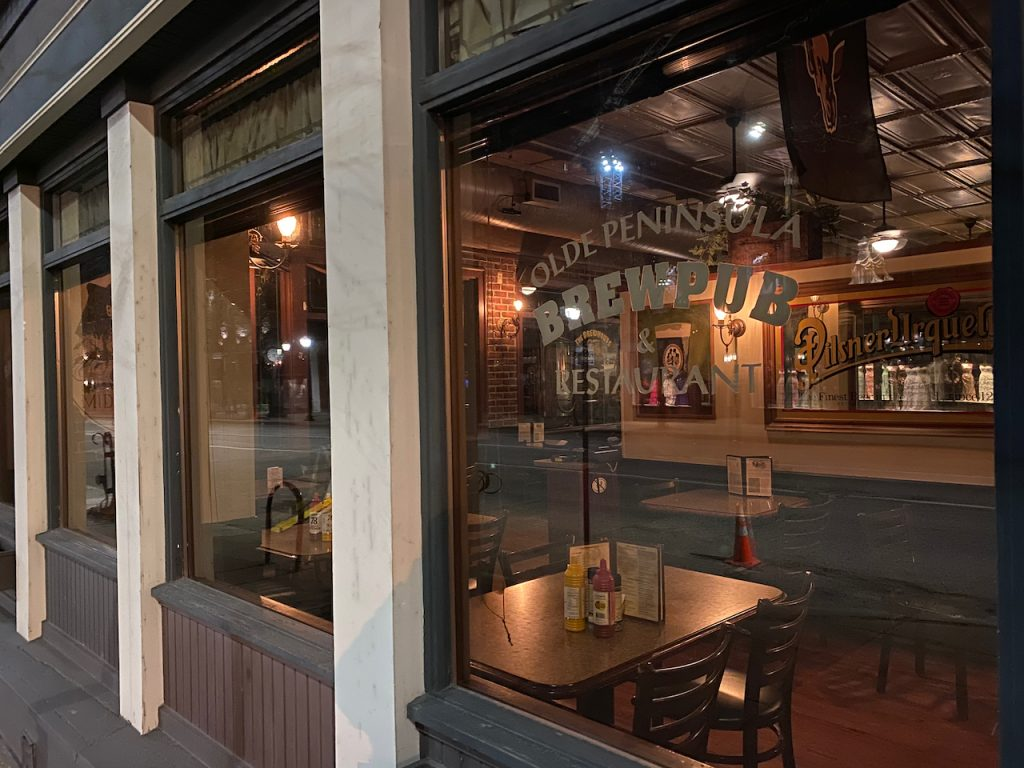 the side window of a restaurant showing empty tables and chairs inside