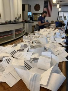 Brewery owner stands in front of lots and lots of order receipts