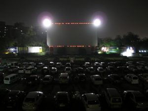 Cars parked in front of a movie screen