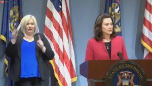 Governor Gretchen Whitmer stands behind a podium with sign language interpreter.