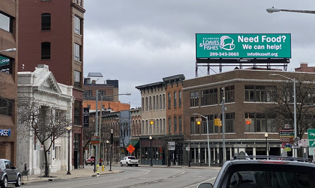 A billboard for Kalamazoo Loaves and Fishes on top of a building
