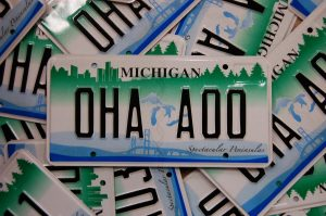 a michigan license plate on top of a pile of license plates