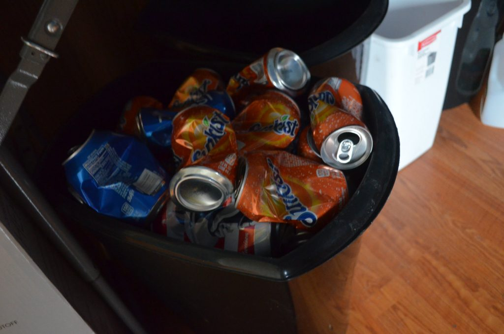 a black trash bin filled with crushed soda cans