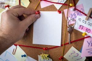 A person tacks a note to a pinboard covered in red thread.