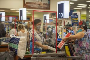 a woman with a face mask stands behind a clear protective shield scanning groceries