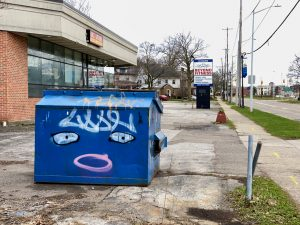 a blue dumpster with a face painted on it stands in front of a gym