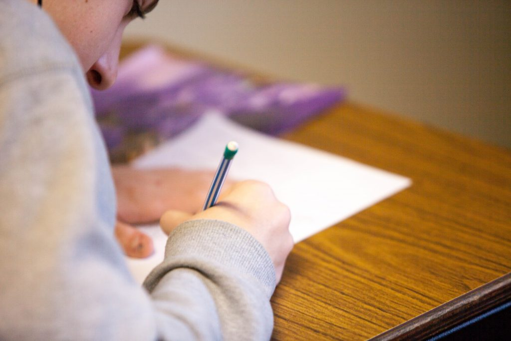 a student fills out answers on a test with a pencil
