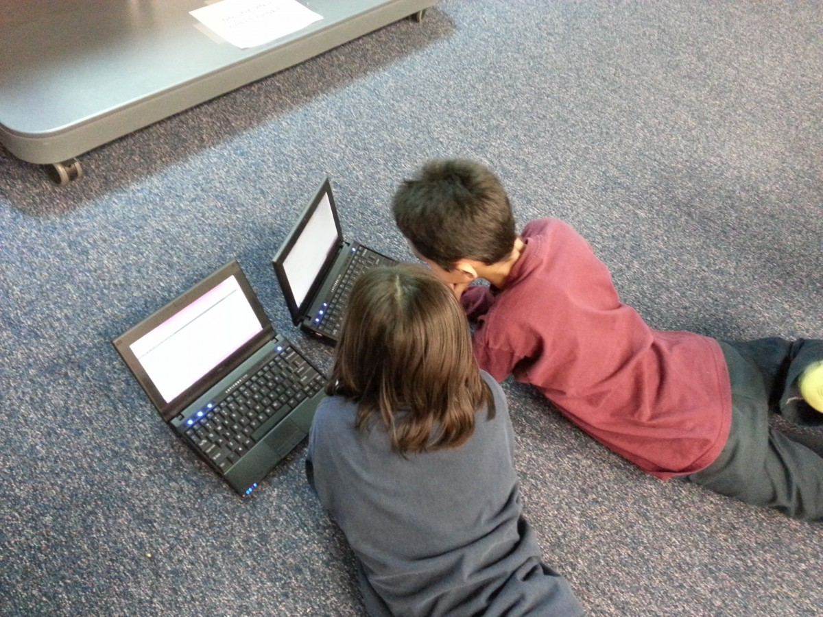 two children laying on the floor looking at laptop screens
