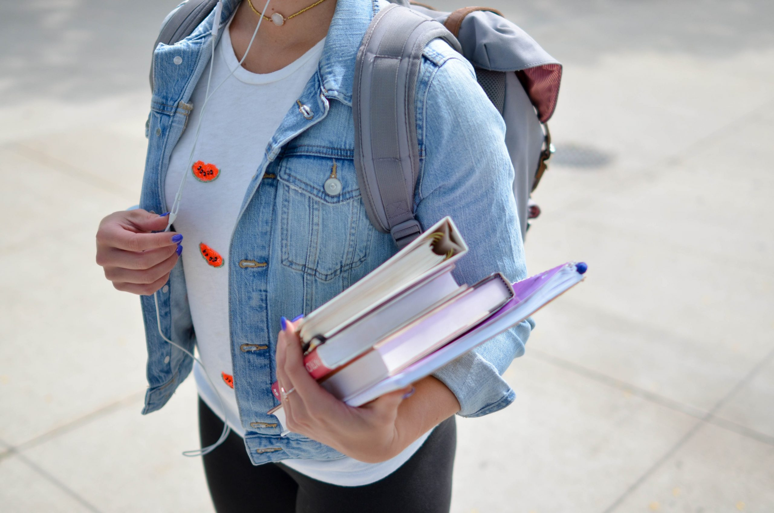 a young woman holds a stack of textbooks