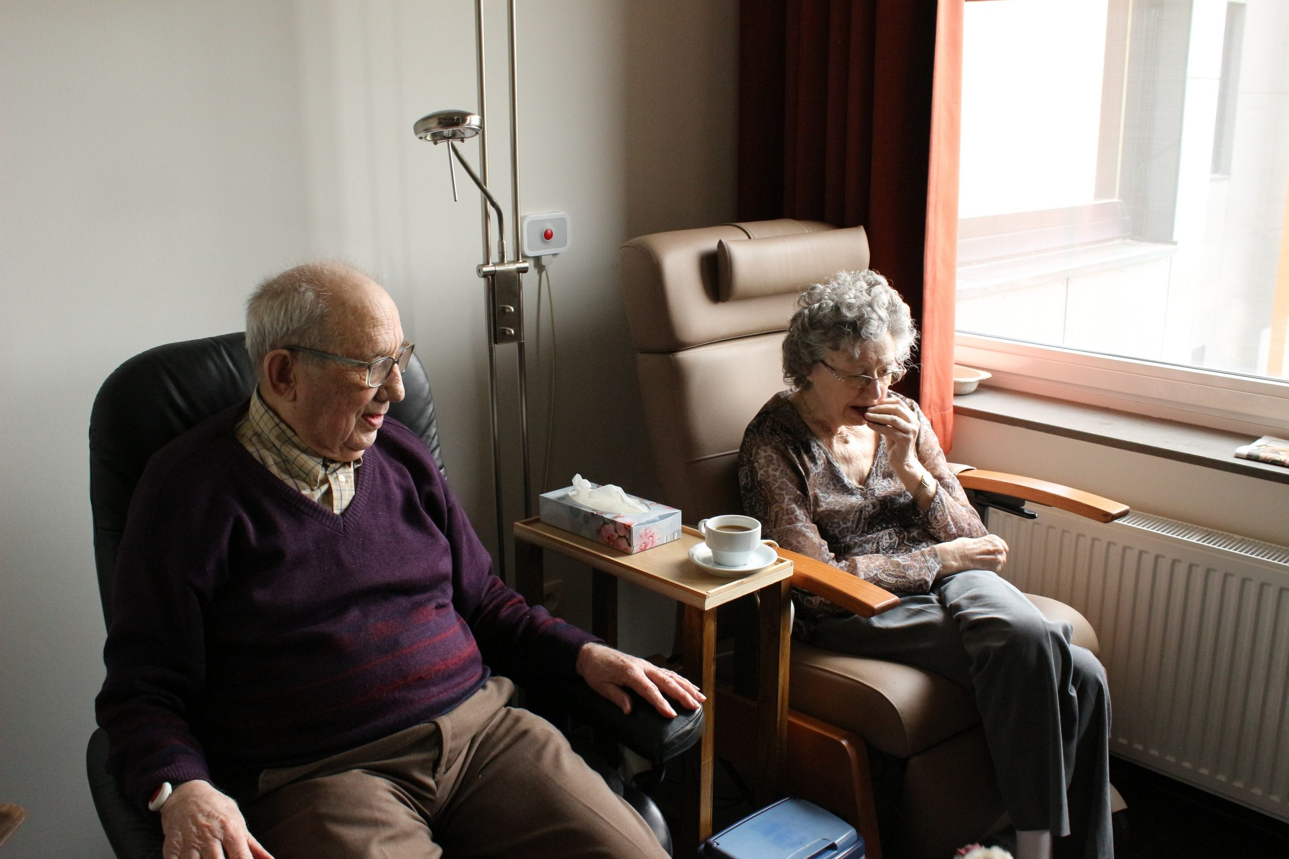 an elderly woman and an elderly man sit in chairs next to each other in a hospital room