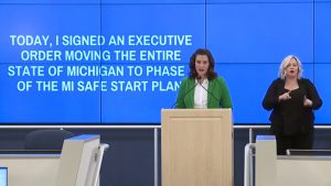 """Governor Gretchen Whitmer stands behind a podium and in front of a blue screen that reads """"today I signed an executive order moving the entire state of michigan to phase 4 of the MI safe start plan"""""""