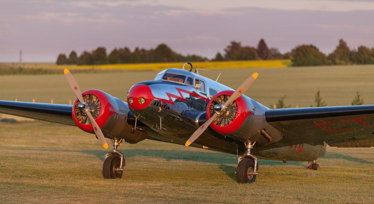 a propeller-powered airplane on a grass runway