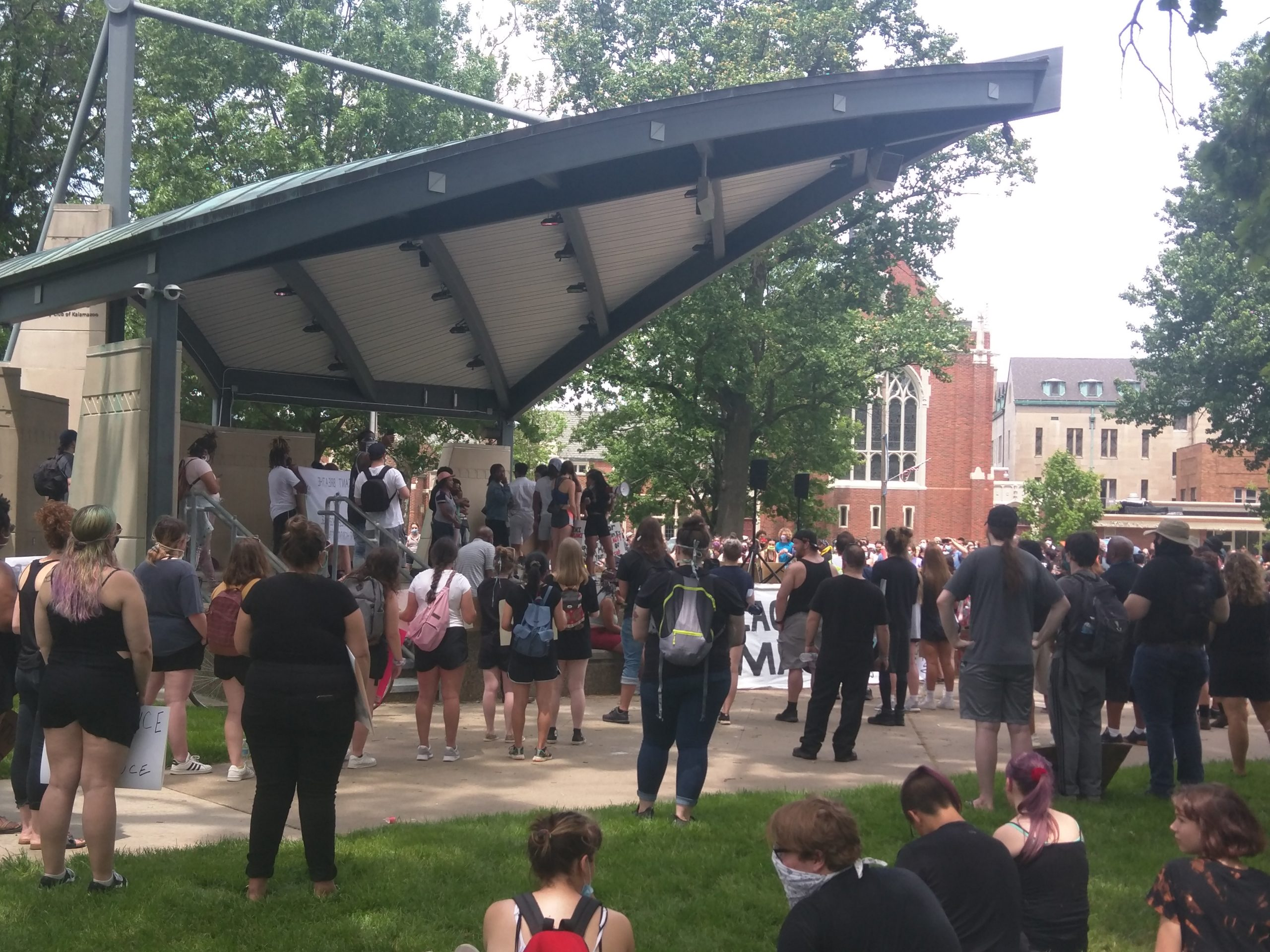 A crowd of people stands in front of an outdoor stage where people are speaking