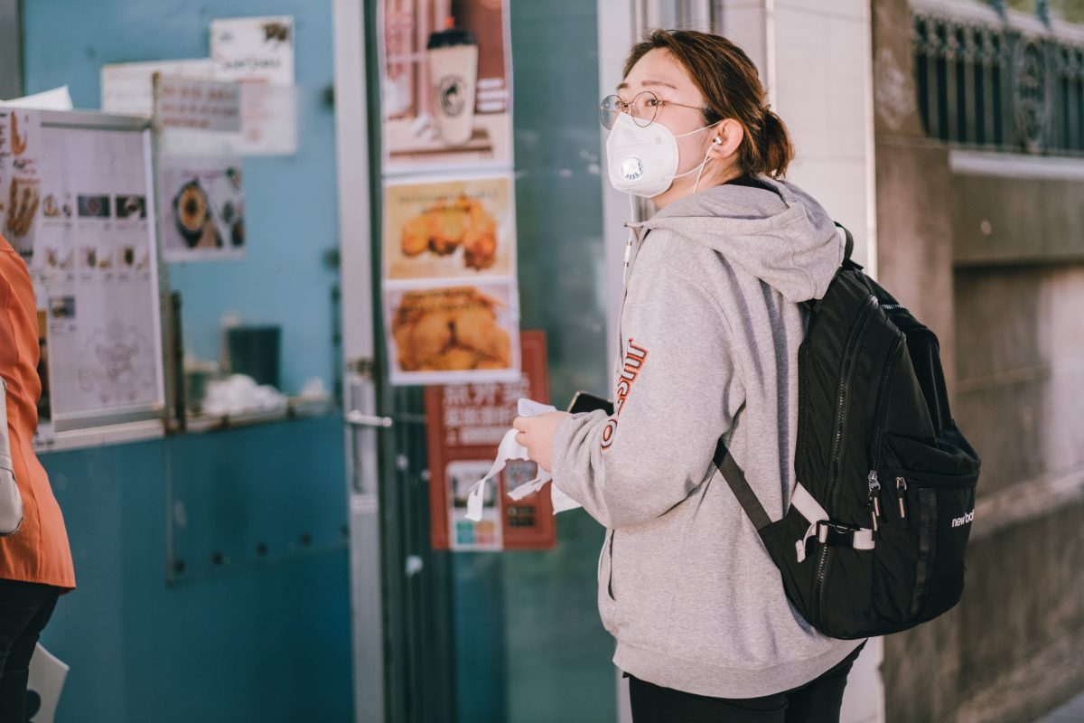 a woman in a gray hoodie wearing a face mask stands in front of a shop door