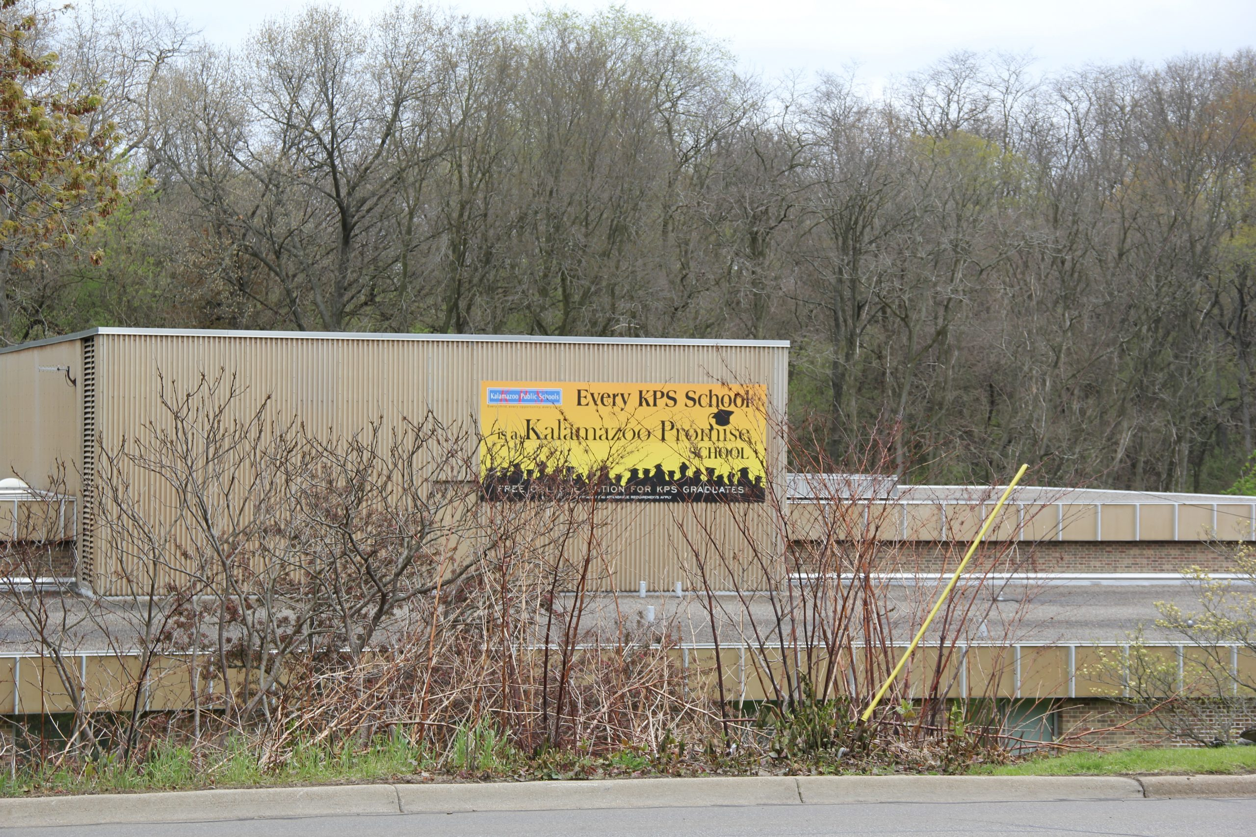 """a sign on a brick building that reads """"every KPS school is a Kalamazoo Promise school."""""""