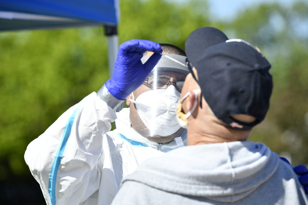 a person in a mask and protective gear sticks a cotton swab up a man's nose to test for COVID-19