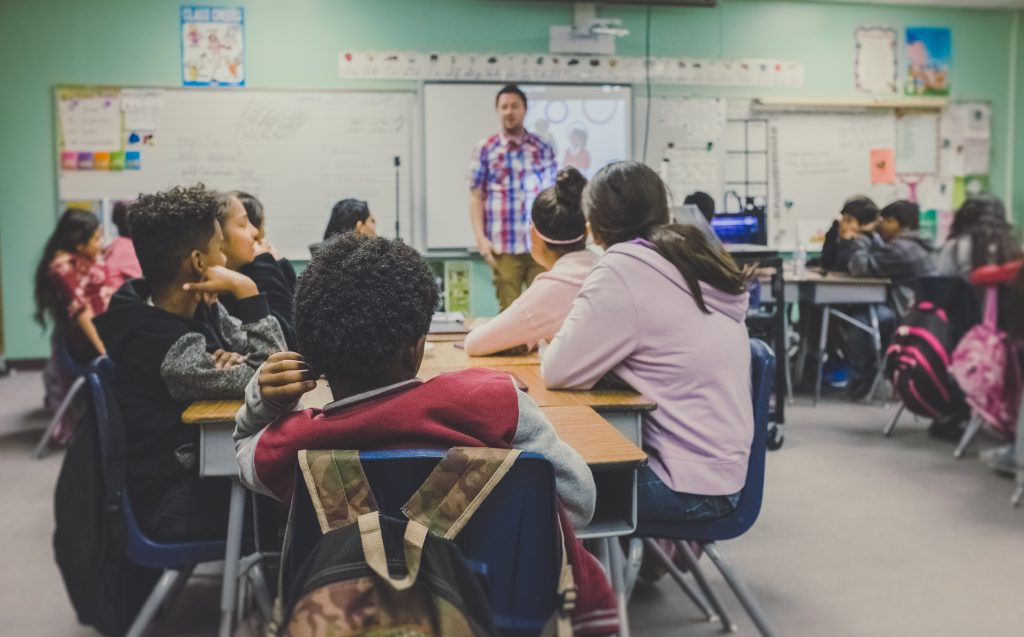 kids sit at desks in a classroom while a grown man in the background teaches