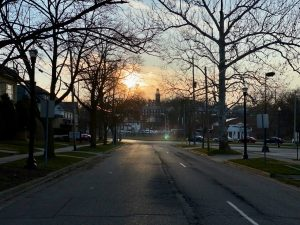 a streetscape leading toward a sunset