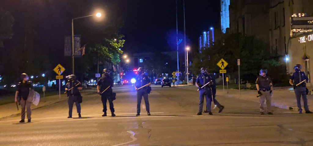 Police officers in Kalamazoo wait for protesters.