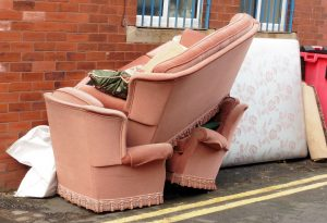 a pink couch and chairs are stacked on the side of the road outside a building
