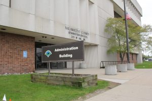 """a sign in front of a cement building reads """"Administration Building"""""""