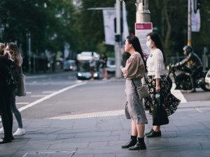 people waiting to cross the street. one has a face mask on, another doesn't.
