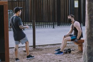 two man in face masks working out in the park during a coronavirus lockdown