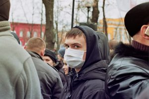 a person wearing surgical mask in a crowd