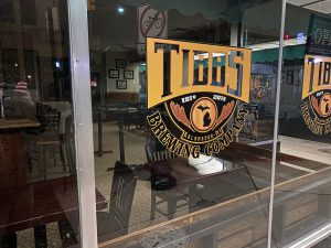 """a sign on a window reads """"Tibbs Brewing Company"""""""
