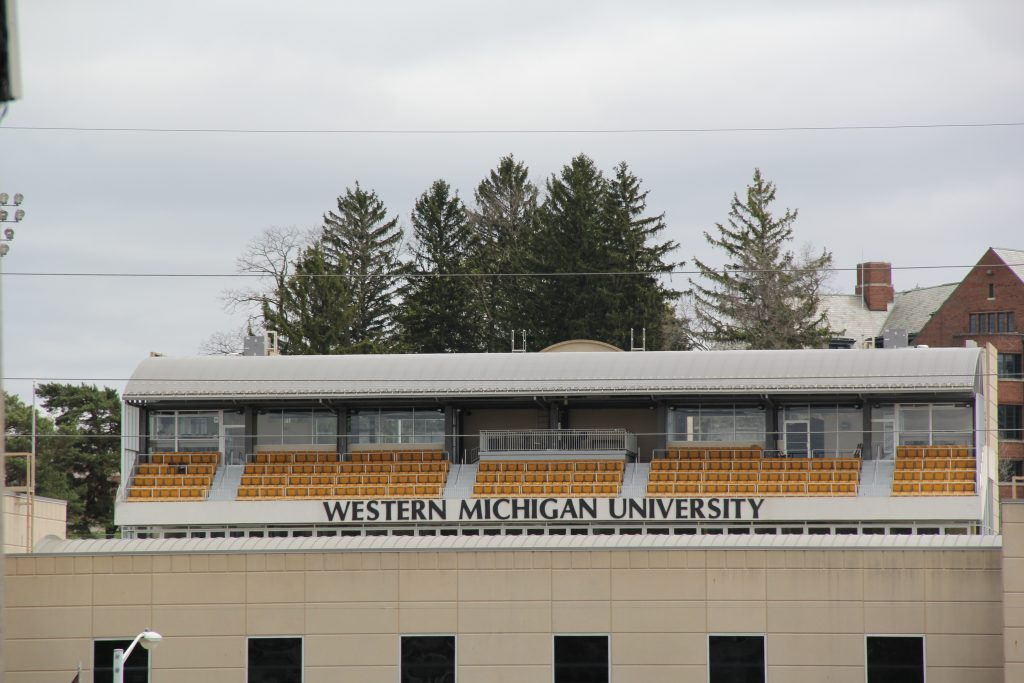 "a row of outdoor seats behind a sign that reads ""western michigan university"""