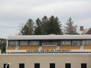"""a row of outdoor seats behind a sign that reads """"western michigan university"""""""