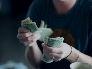 a woman counts a stack of dollar bills