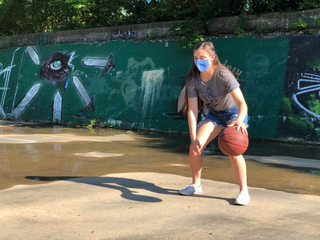a woman in a mask dribbles a basketball