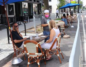 a man and a woman sit at a table outdoors with masks on while a waiter with a mask takes their order