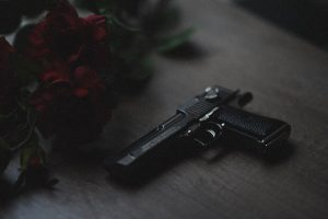 a black handgun next to red roses