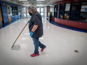 a woman pushes a mop in a school hallway while wearing a mask