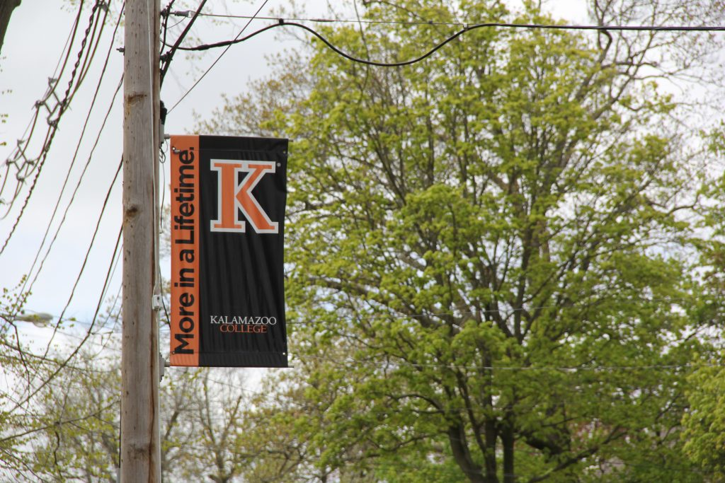 """a flag on a light pole with words that read """"More in a lifetime. Kalamazoo College"""""""