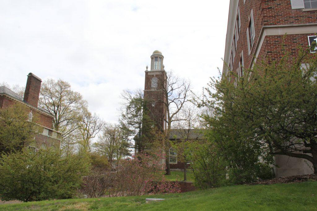 a chapel spire rises up between brick buildings