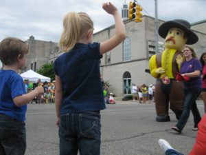 two children wave at a man in an inflatable cowboy costume