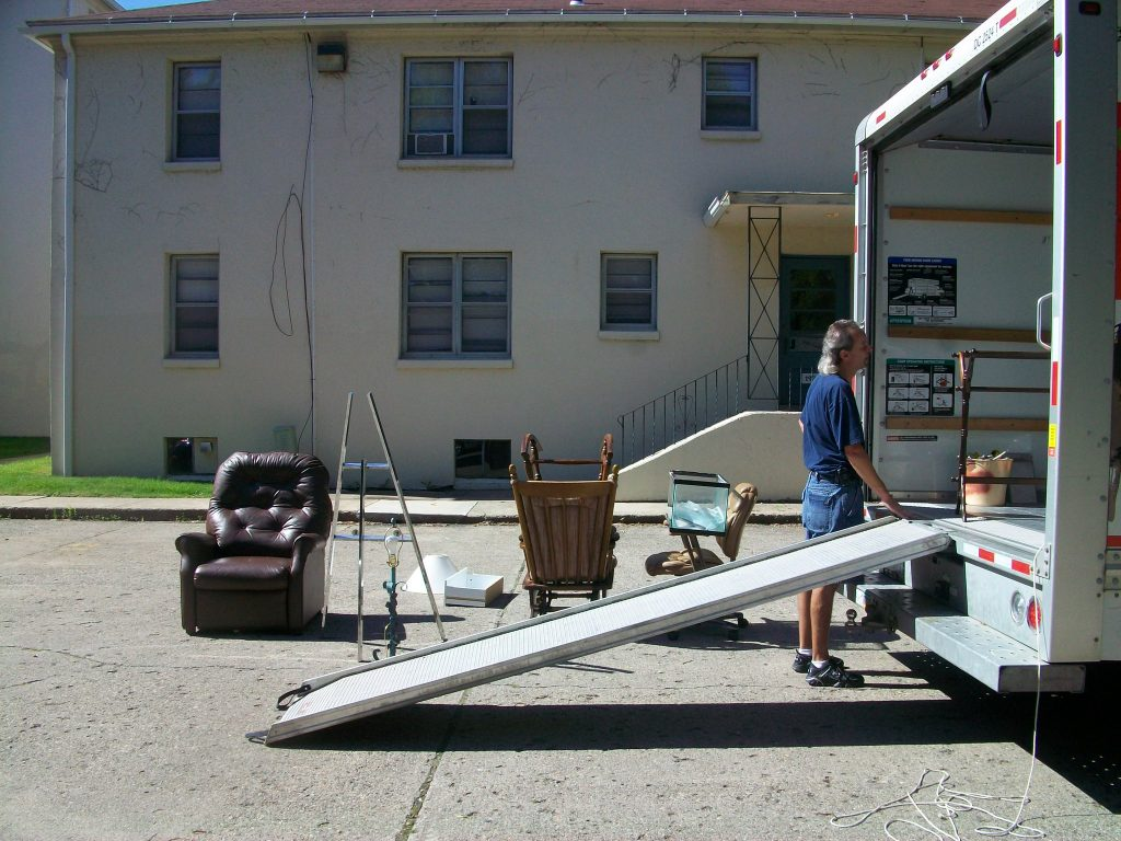 a man stands behind a rental truck with some furniture unloaded behind him