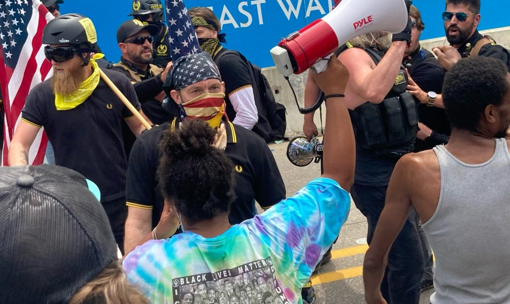 a white man with an American flag bandana stands among a disorderly crowd