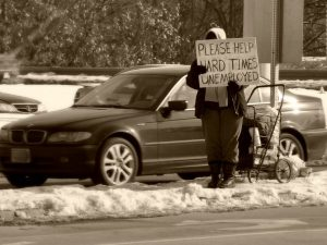 "a person stands in a road with a sign that reads ""Please Help. Hard Times. Unemployed"""