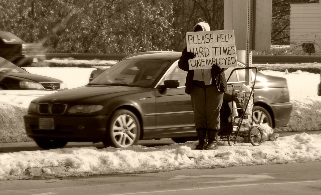 """a person stands in a road with a sign that reads """"Please Help. Hard Times. Unemployed"""""""