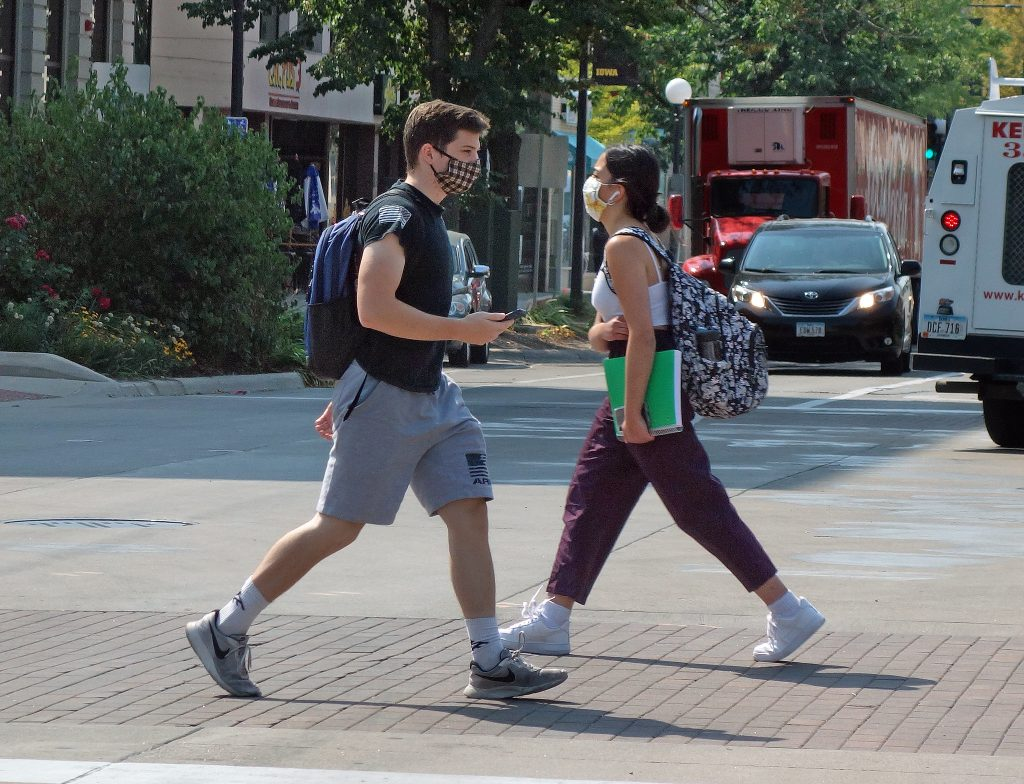 two college students walk past each other wearing face masks