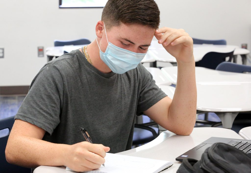 a boy in a face mask takes notes