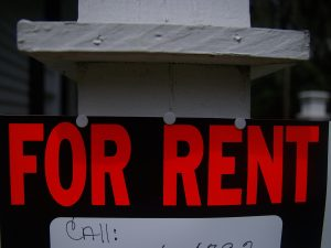"a sign reads ""for rent"""