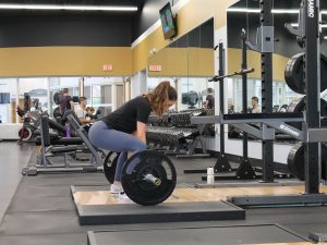 a woman crouches to lift weights in an uncrowded gym