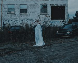 A person in a ghost costume standing alone